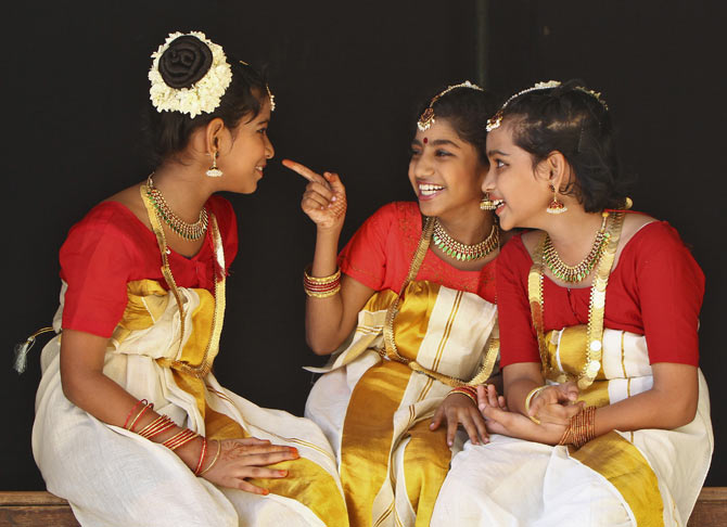 School girls wearing traditional costume share a laugh backstage as they wait to perform during festivities marking the start of the annual harvest festival of Onam in the southern Indian city of Chennai