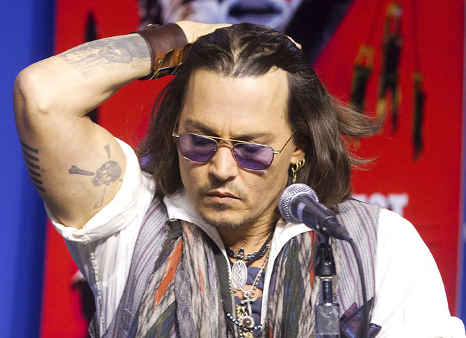 Actor Johnny Depp reveals his various tattoos during a news conference to promote his film West of Memphis.