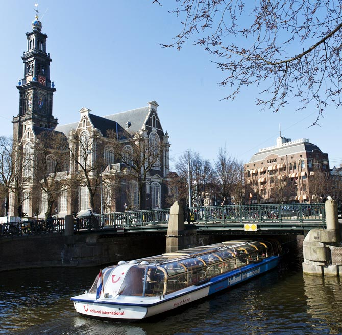 A tourist boat passes under a bridge next to the Westerkerk church in Amsterdam
