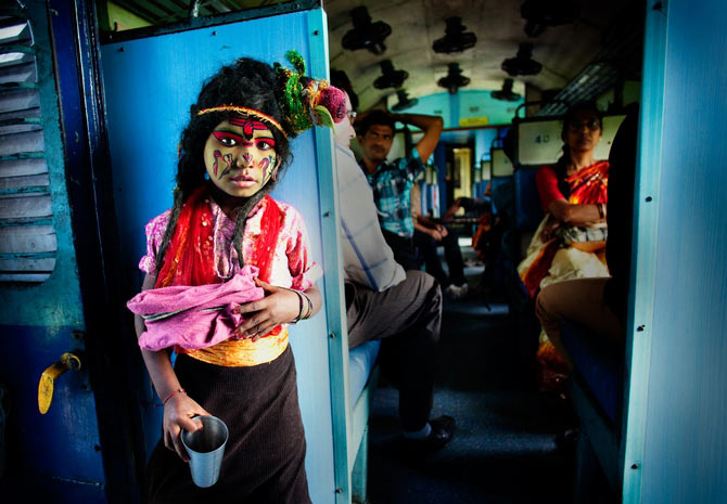 A boy dressed as Lord Shiva, begs for alms in a train compartment in West Bengal. This picture was adjudged the best in the 'People' category.
