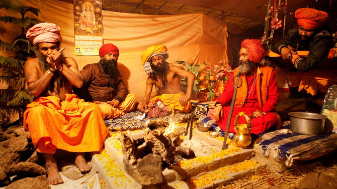 Hindu saints congregate at the 2013 Kumbh Mela amidst strong opium smell and the smoke of burning wood to decide their next day's programme.