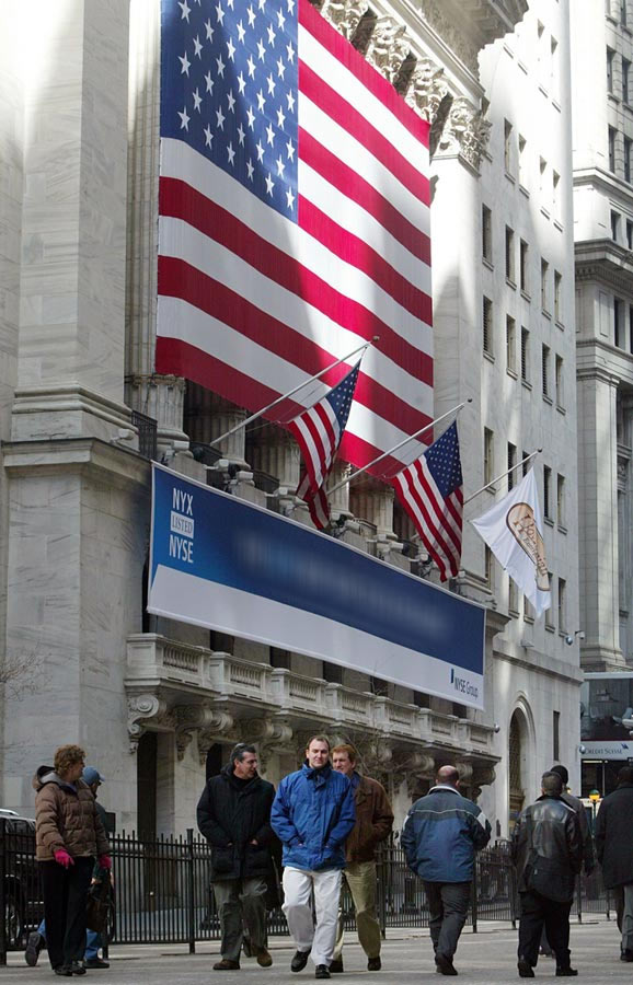 People walk in front of the NYSE