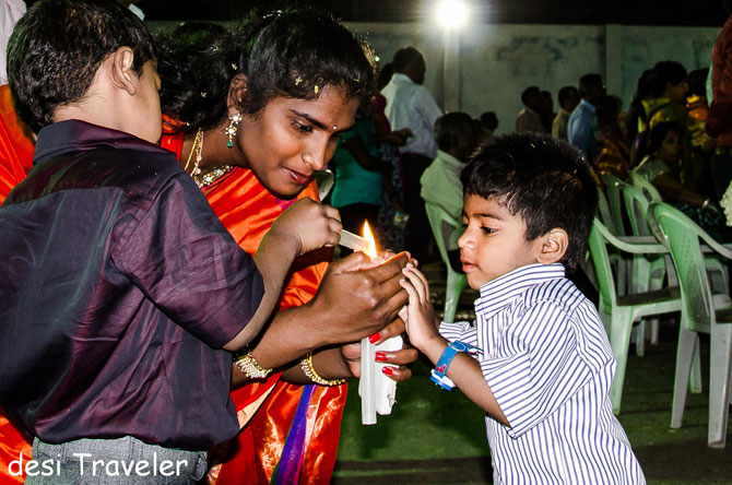 A mother helps her sons light the candles ahead of the mass.