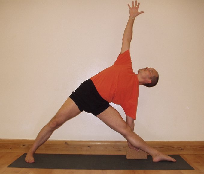 A student performing Uttitha Trikonasana, triangle pose, one of the basic standing poses in Iyengar Yoga.