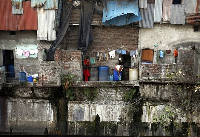 Women wash themselves outside their shanty in Dharavi.