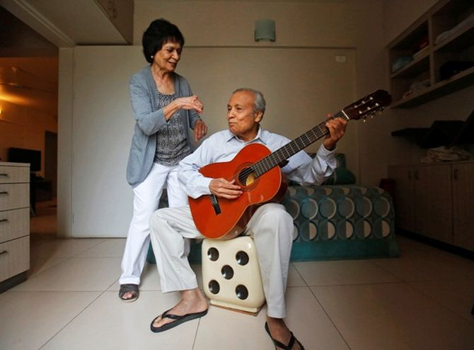 Aruna Gokhale (L), 81, watches as her husband Vidyadhar Gokhale, 84, plays guitar.