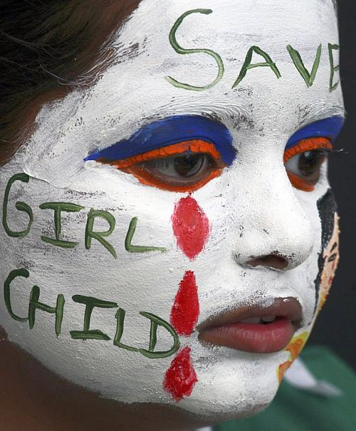 A girl with her face painted with an awareness message on female foeticide.