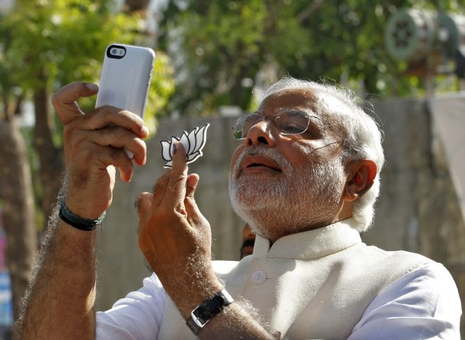 Prime Minister Narendra Modi takes a 'selfie' with a mobile phone after casting his vote.