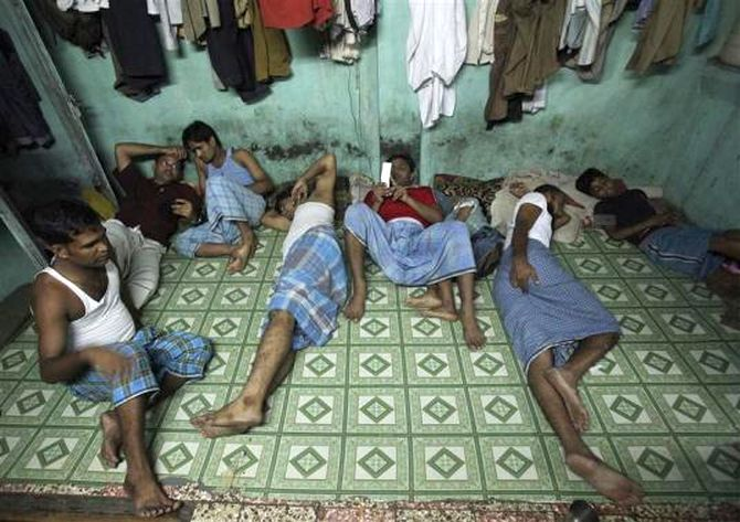 Migrant workers rest inside their one room dwelling in a residential area in Mumbai.
