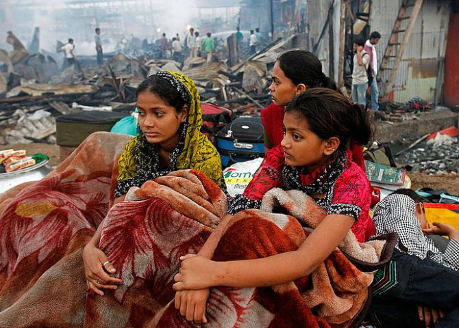 Rubina Ali ( R ), who acted as young Latika in the Oscar-winning film Slumdog Millionaire, sits with her family amid the ruins of the Gharib Nagar slum in Mumbai. A fire gutted the slum.