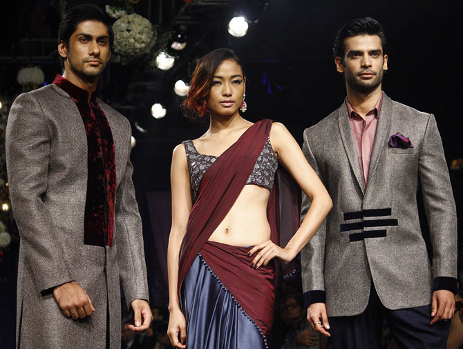 Katheleno Kenze is flanked by two hunks during Manish Malhotra's show
