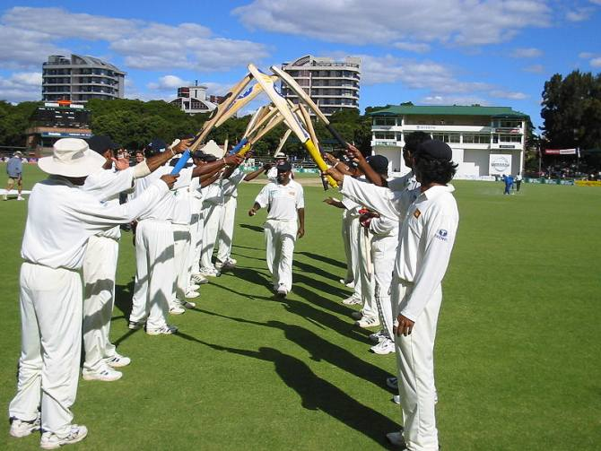 Sri Lankan players give teammate Muttiah Muralitharan a guard of honour in Harare after he broke Courtney Walsh's record for most Test wickets.