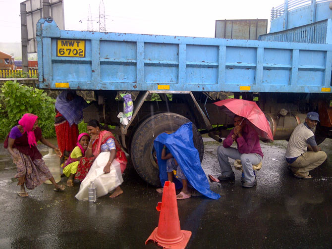A group of labourers taking shelter from rain
