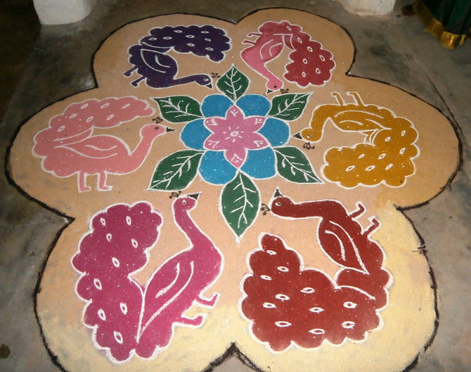 A colourful kolam is drawn in front of the home to welcome Lord Ganesha