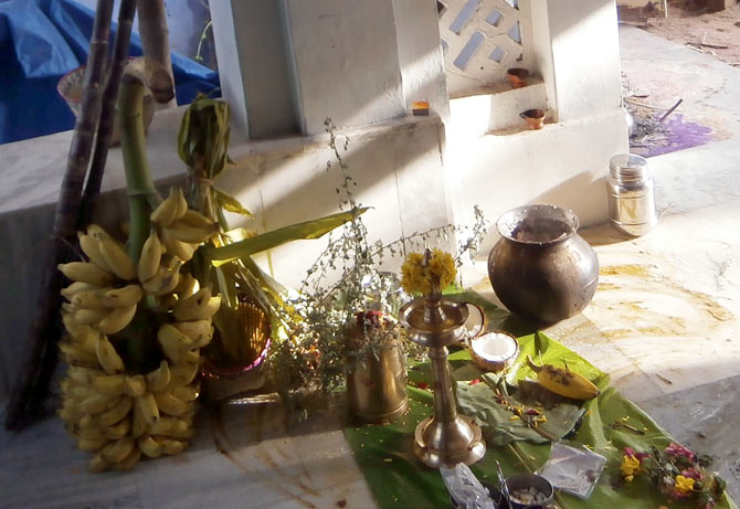 An offering of rice, bananas, betel leaf and sugarcane is kept outside the house