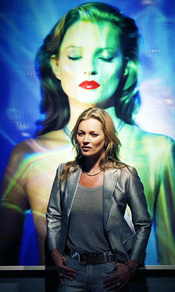 Model Kate Moss poses with She's Light (Laser 3), by photographer Chris Levine at Christie's auction house in London.