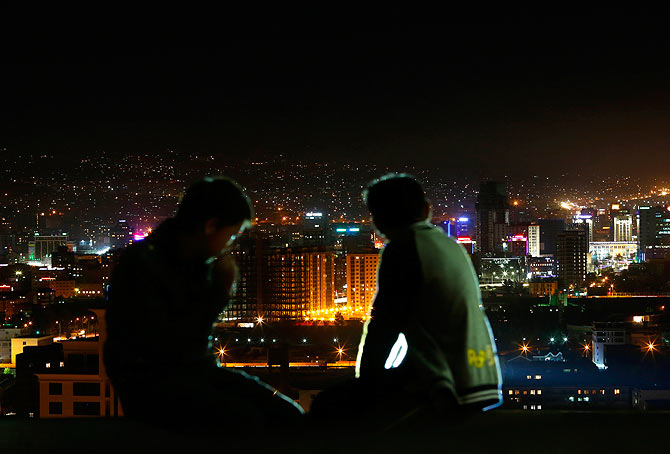 Teenagers look out at the night skyline of Mongolia's city capital Ulan Bator