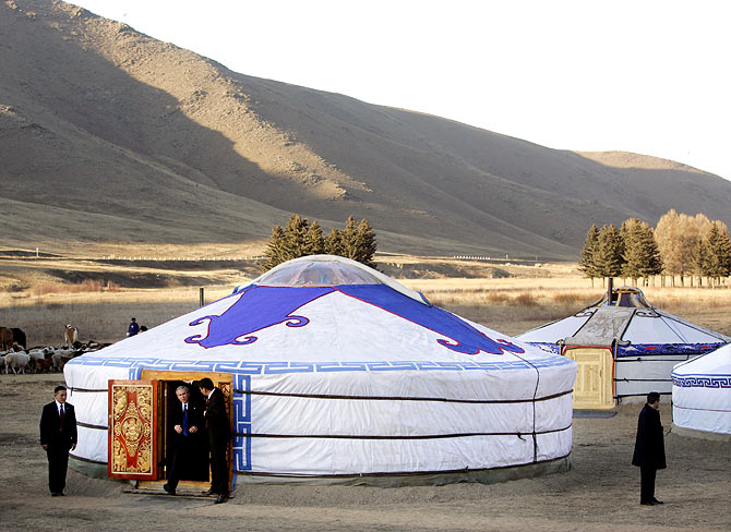 U.S. President George W. Bush steps from a Ger, a felt tent, while visiting Ikh Tenger in Ulan Bator, Mongolia, November 21, 2005. Bush thanked Mongolia on Monday for sending troops to Iraq in a visit steeped in the traditional culture of a nomadic land that produced Genghis Khan.