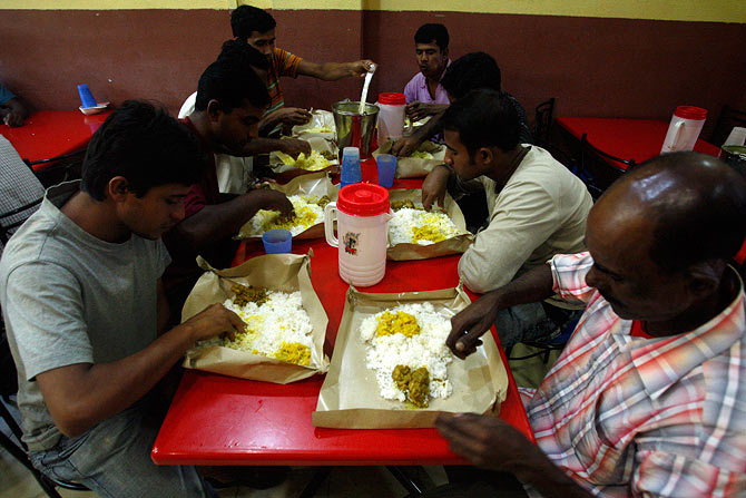 Labourers from Bangladesh eat dinner at a restaurant in Singapore's Little India district January 13, 2009. The Free Meals Program, run by the volunteer group Transient Workers Count Too, provides one meal a day on weekdays for migrant workers who cannot afford to feed themselves, and is financed entirely by fundraising and donations.