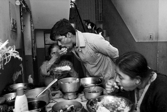 Sandip Karan takes a meal in the midst of treatment. He lives with his mother Saraswati (left) and wife Moumita (right). He has a child, not seen in the photograph.