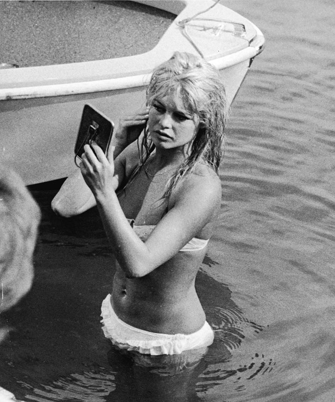A file picture of Brigitte Bardot looking at her reflection in a mirror, while standing in the waters of Lake Leman.