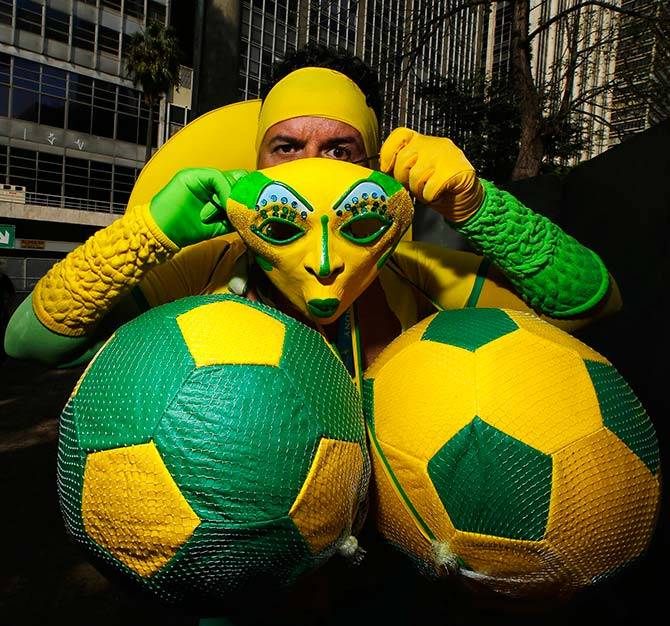 A Brazil fan puts on his costume before watching a telecast of the 2014 World Cup soccer match between Brazil and Chile, at a FIFA fan area in Sao Paulo June 28, 2014.