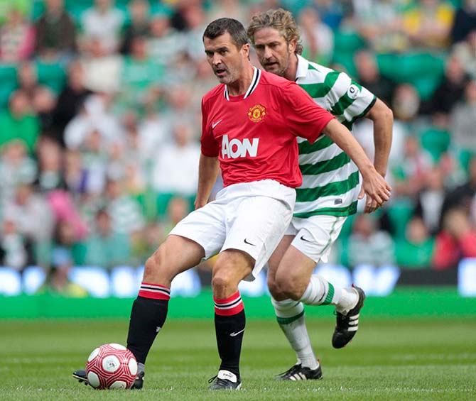 Manchester United Legends Roy Keane passes the ball as Celtic Legends Gerard Butler challenges during their charity soccer match at Celtic Park stadium in Glasgow, Scotland August 9, 2011.