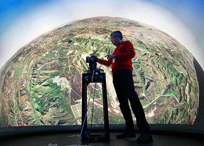 Geert Matthys, research and development manager at Barco, a Belgian company specialising in high-definition projectors and displays, gives an explanation inside a fully immersive 360-degree flight simulator in Kuurne October 11, 2011. Barco has unveiled the ultimate fighter jet training tool designed to reproduce reality exactly as a pilot sees it. The dome is the first ever flight simulator to give trainee pilots a full 360 degree view of the world as they conduct virtual missions, said Barco.