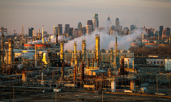 The Philadelphia Energy Solutions oil refinery owned by The Carlyle Group is seen at sunset in front of the Philadelphia skyline.