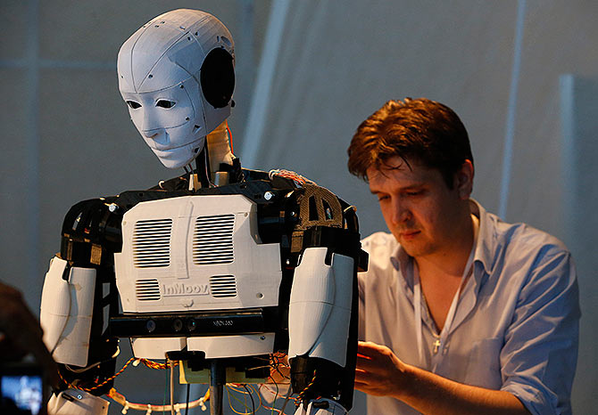 A technician makes adjustments to the 'Inmoov' robot from Russia during the 'Robot Ball' scientific exhibition in Moscow
