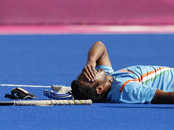 India's Raghunath Vr lies on the pitch after being injured during the men's Group B hockey match against Germany at the London 2012 Olympic Games.