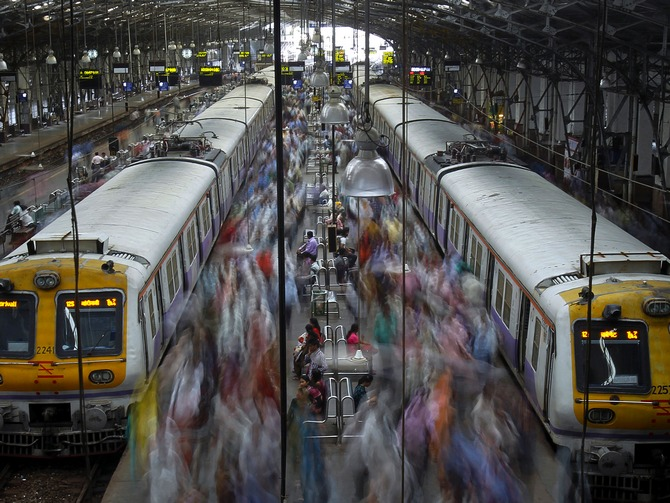Commuters disembark from crowded suburban trains during the morning rush hour at Churchgate railway station in Mumbai.