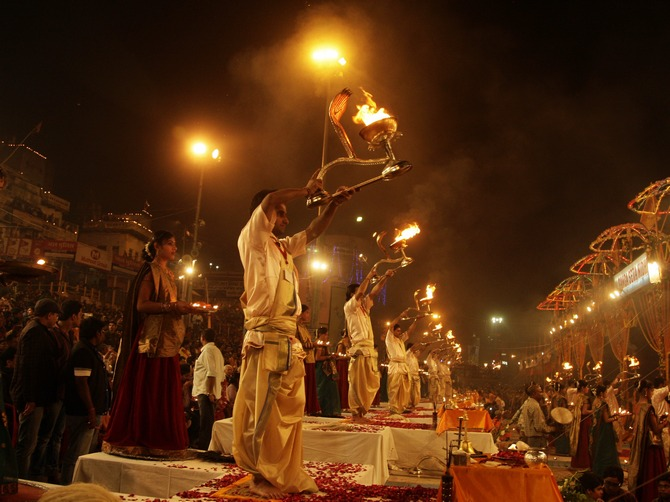 Hindu priests hold oil lamps as they perform prayers on the banks of river Ganges during the Karthik Purnima festival on the occasion of Dev Deepawali at Dasasumerghat in Varanasi.