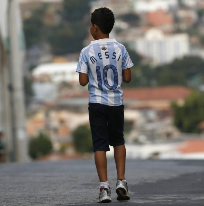 A boy wearing a jersey of Argentine star Lionel Messi walks on a street outside Independencia stadium before the start of the Argentine national team training session in preparation for 2014 World Cup in Belo Horizonte, June 11, 2014.