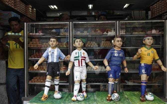 A worker carries sweets next to the models of soccer players that are made of sweets at a bakery shop ahead of the 2014 FIFA World Cup, on the outskirts of Kolkata June 11, 2014. The 2014 World Cup soccer tournament will be held in 12 cities in Brazil from June 12 to July 13.