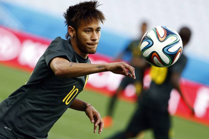 Brazil's Neymar eyes the ball during his team's final practice in Sao Paulo one day before the opening match of the soccer World Cup between Brazil and Croatia June 11, 2014