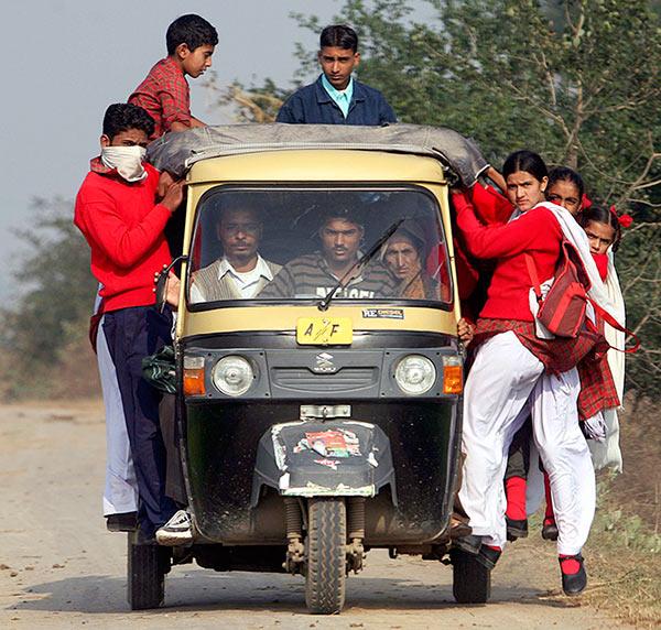School children travel on a motorised rickshaw in Gharana village, about 30 km (19 miles) southwest of Jammu December 11, 2008.