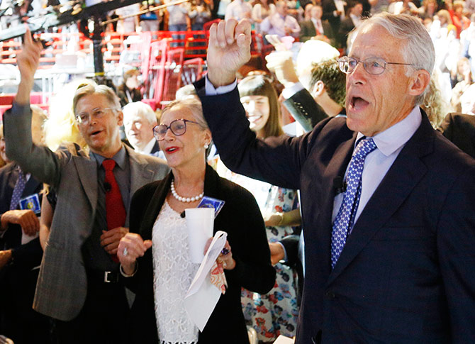Wal-Mart Stores family members (L - R) Jim Walton, Alice Walton and Chairman of the Board of Directors Rob Walton recite the Walmart cheer at the annual shareholders meeting.