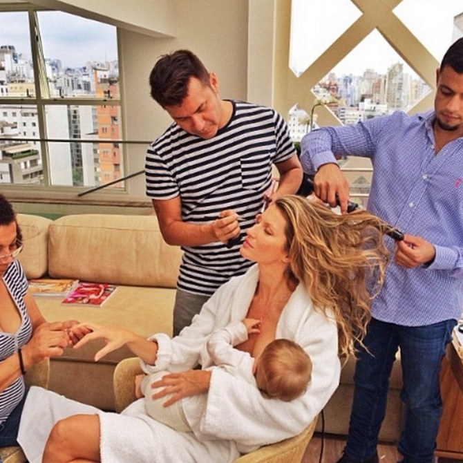 Gisele nurses her child as she readies for photoshoot.
