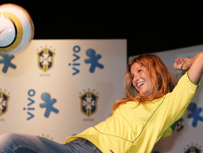 Gisele knees a soccer ball during the presentation of a new sponsor for the Brazilian national soccer team.