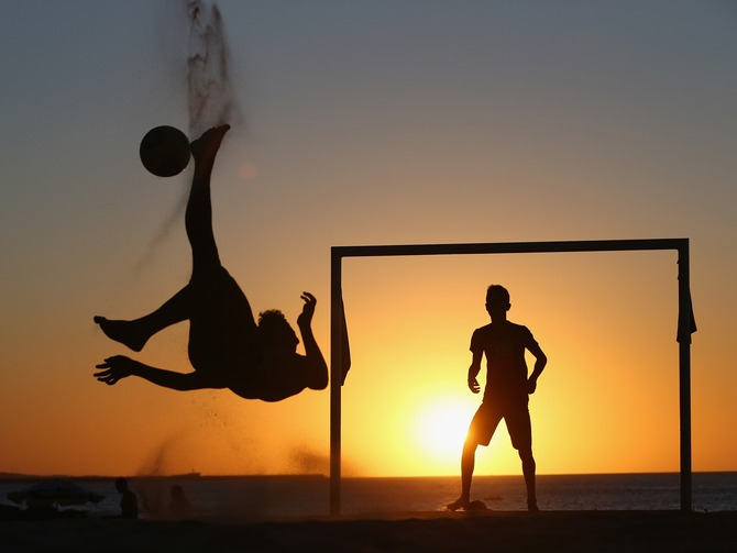 Locals play football at the Iracemar beach in Fortaleza, Brazil.