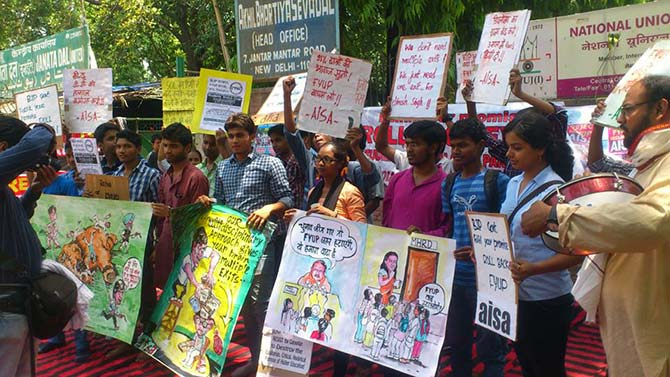 Students from Delhi University hold placards to explain