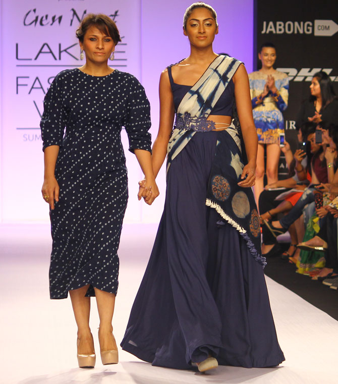 Divya Sheth walks with a model wearing one of her creations