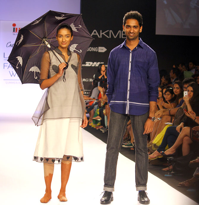 Sreejith Jeevan poses next to a model wearing his creation