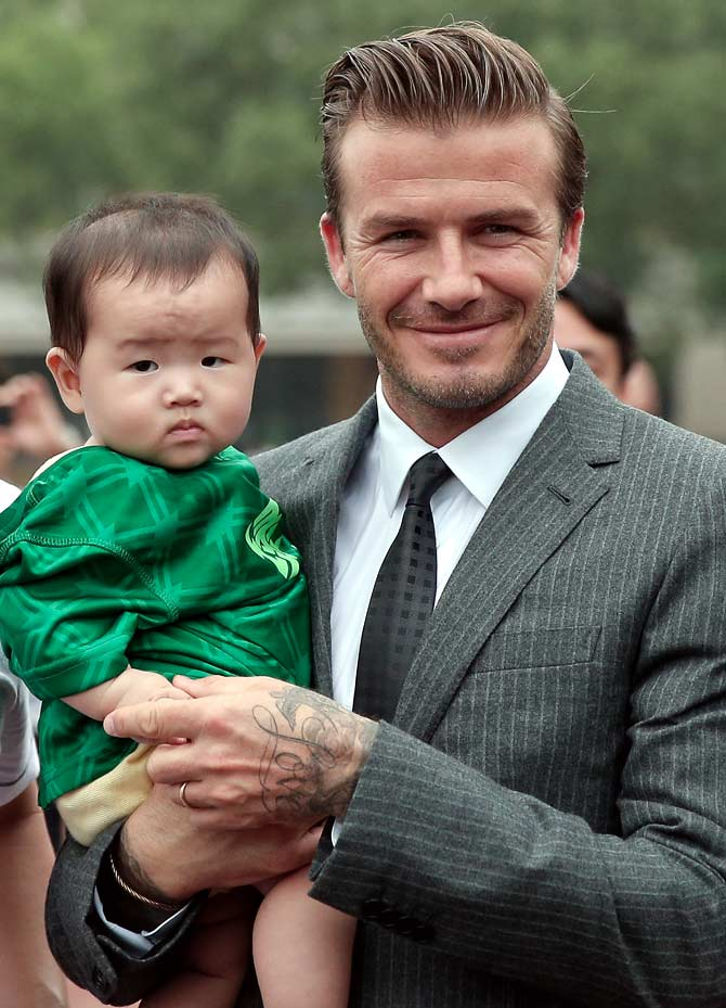 David Beckham poses with a young fan during his visit to Hangzhou Greentown club on in Hangzhou, China.