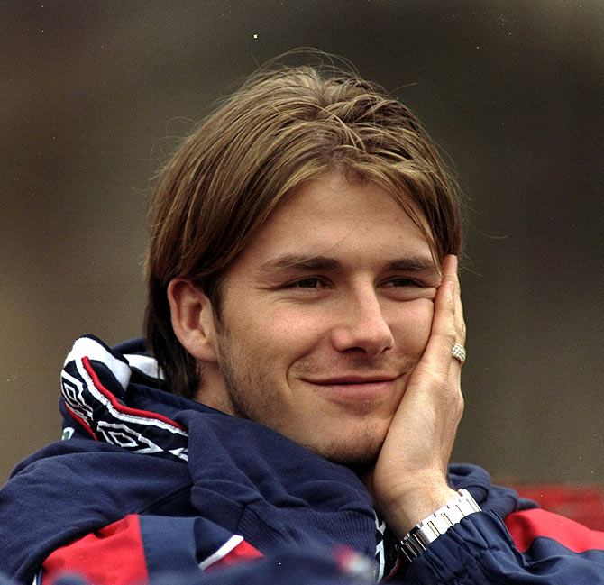 A 1998 picture of David Beckham and Manchester United gives a cheeky smile during an England training session before the friendly against Switzerland.