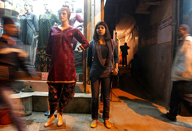 A young girl stands outside a store in New Delhi selling traditional Indian outfits.