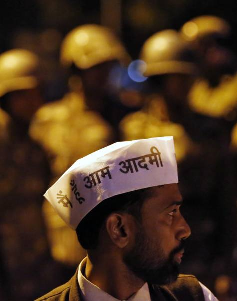 A supporter of Aam Aadmi (Common Man) Party (AAP) stands in front of Indian policemen on guard during a protest outside the headquarters of India's main opposition Bharatiya Janata Party (BJP) in New Delhi March 5, 2014. The writing on the caps reads I am a common man.