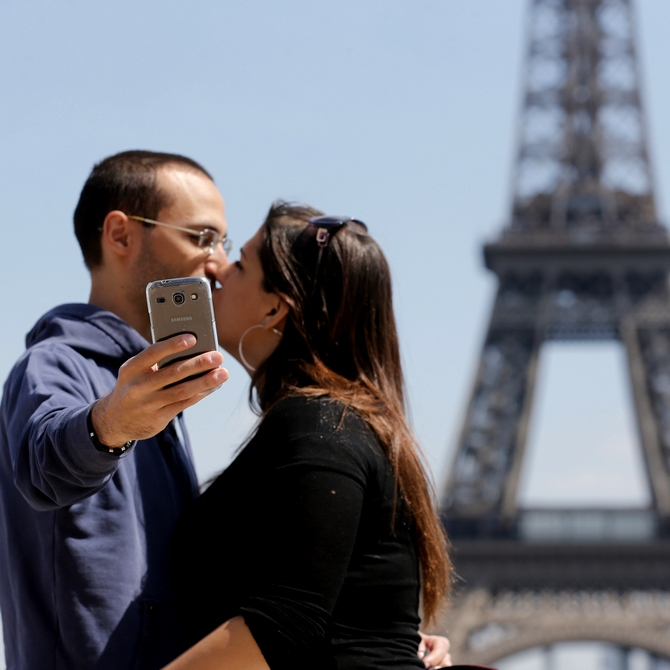A couple takes a selfie before the Eiffel Tower in Paris