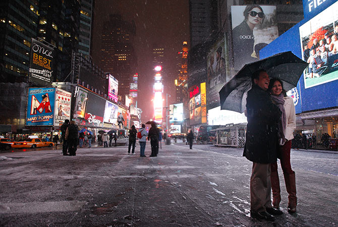A couple have the picture taken during a snow storm in New York's Times Square.